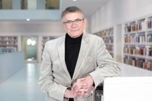 Portrait von Jörg Armbruster, aufgenommen in einer Bibliothek von Christina Kratzenberg