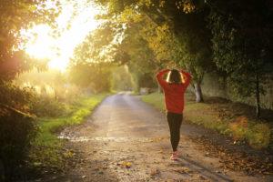 Frau in Sportsachen auf einer Strasse bei Sonnenaufgang